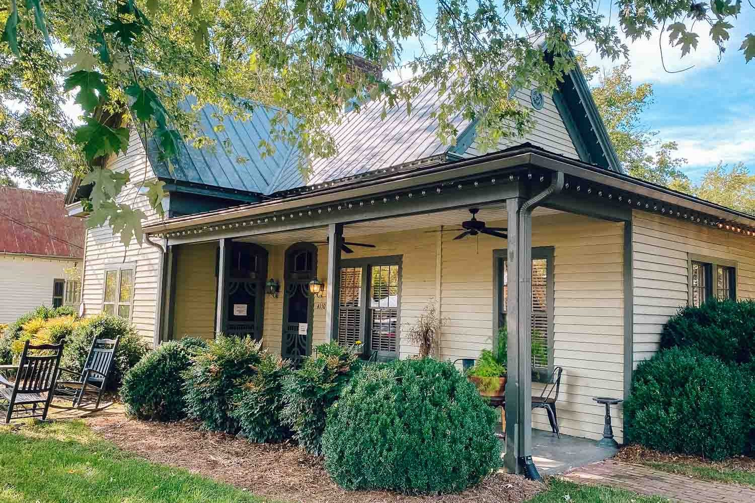 Historic home turned restaurant called 1892 in Leiper's Fork, Tennessee. There is one porch light on and a couple rocking chairs in the yard - things to do in Leiper's Fork