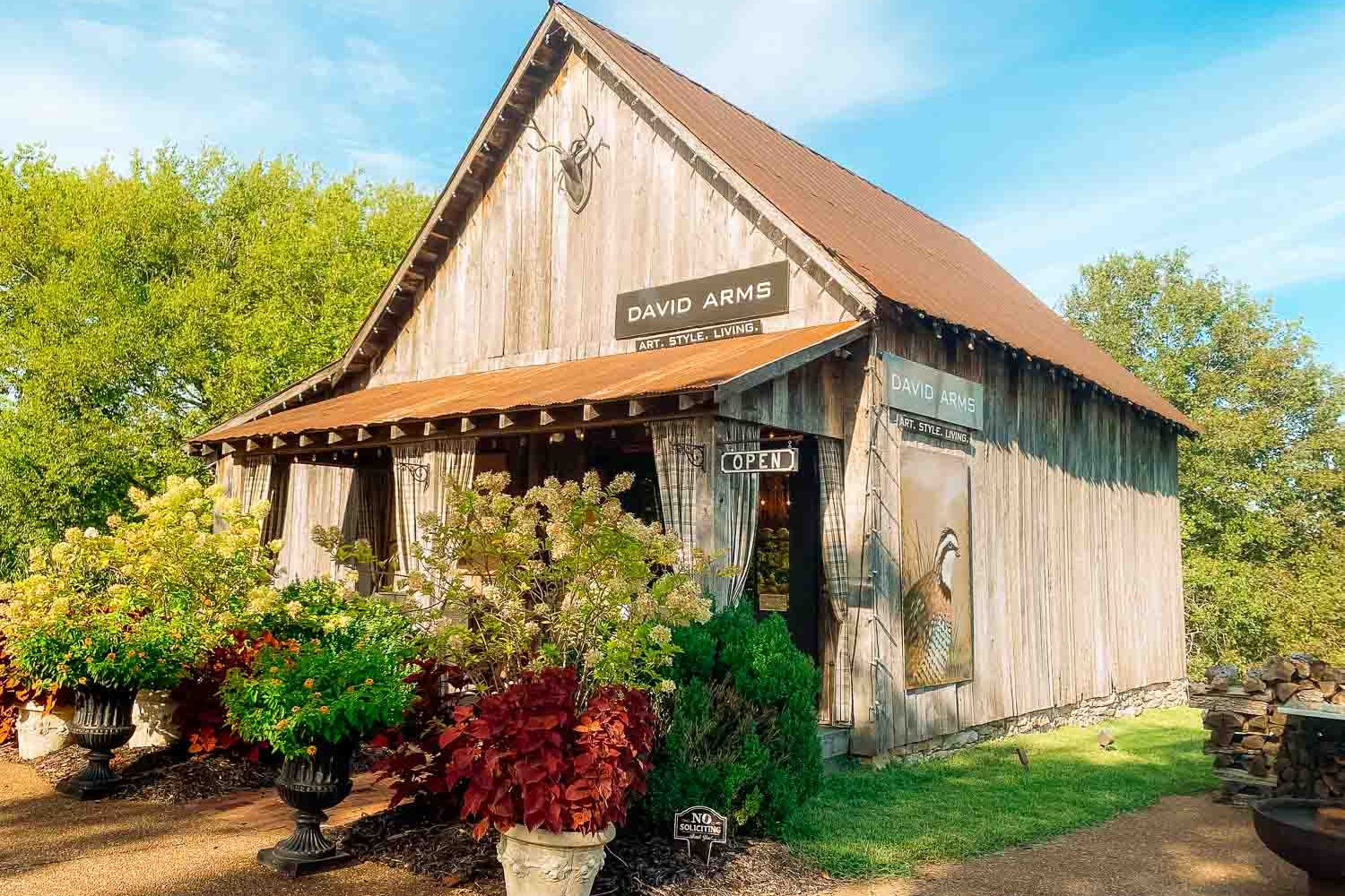 Exterior of David Arms Gallery, a barn surrounded by potted plants, well-trimmed grass, and a pebbled driveway - things to do in Leiper's Fork, TN