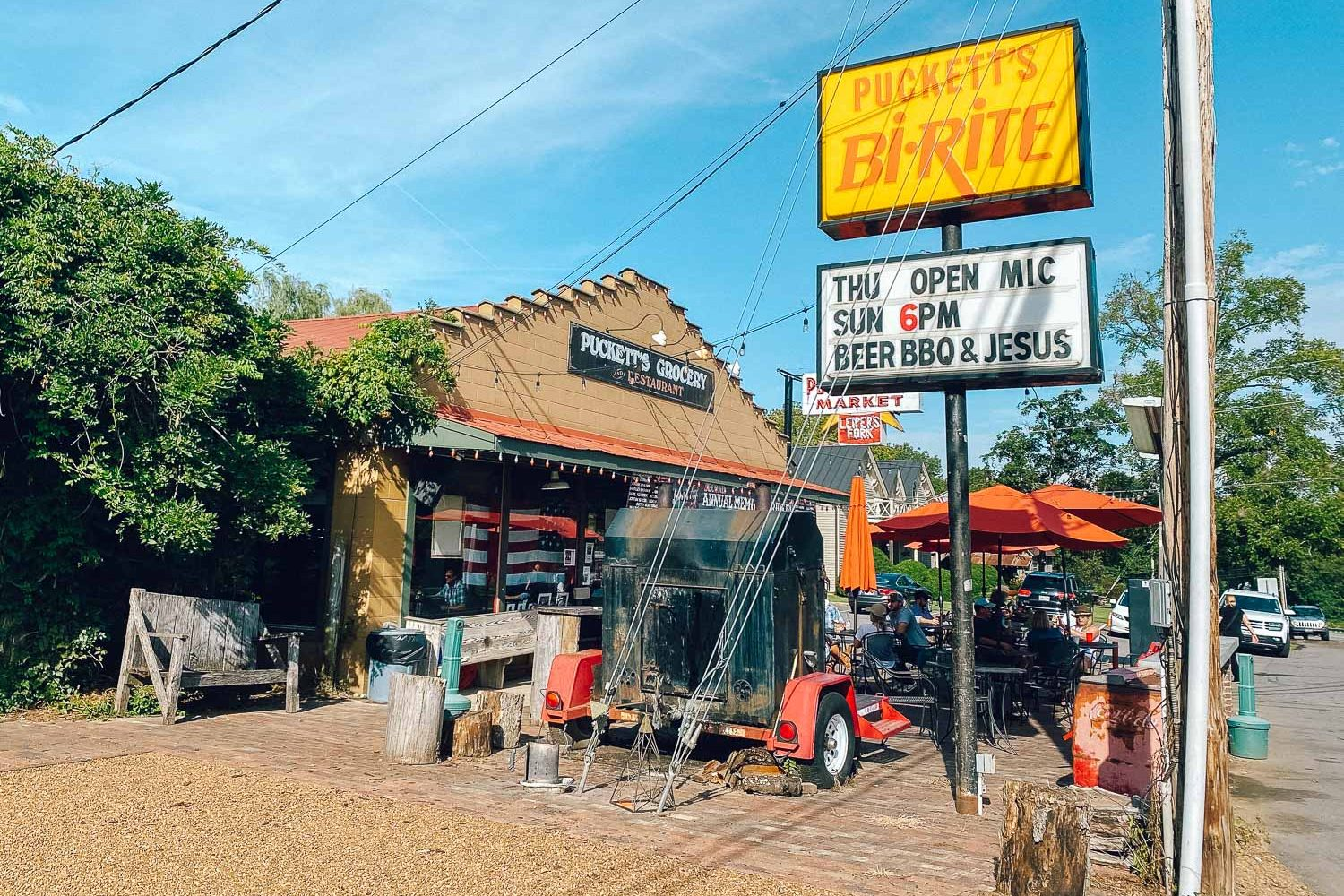 Puckett's of Leiper's Fork, Tennessee. A sign is advertising open mic, plus beer, bbq, and Jesus, all fun things to do in Leiper's Fork - bucket list travel