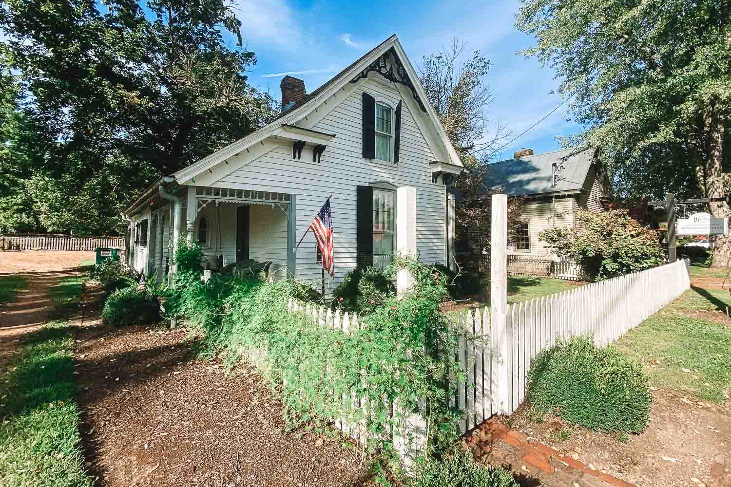 Exterior of white cottage in Leiper's Fork, Tennessee. There is a white picket fence surrounding the cottage and an American flag hanging from the front porch.