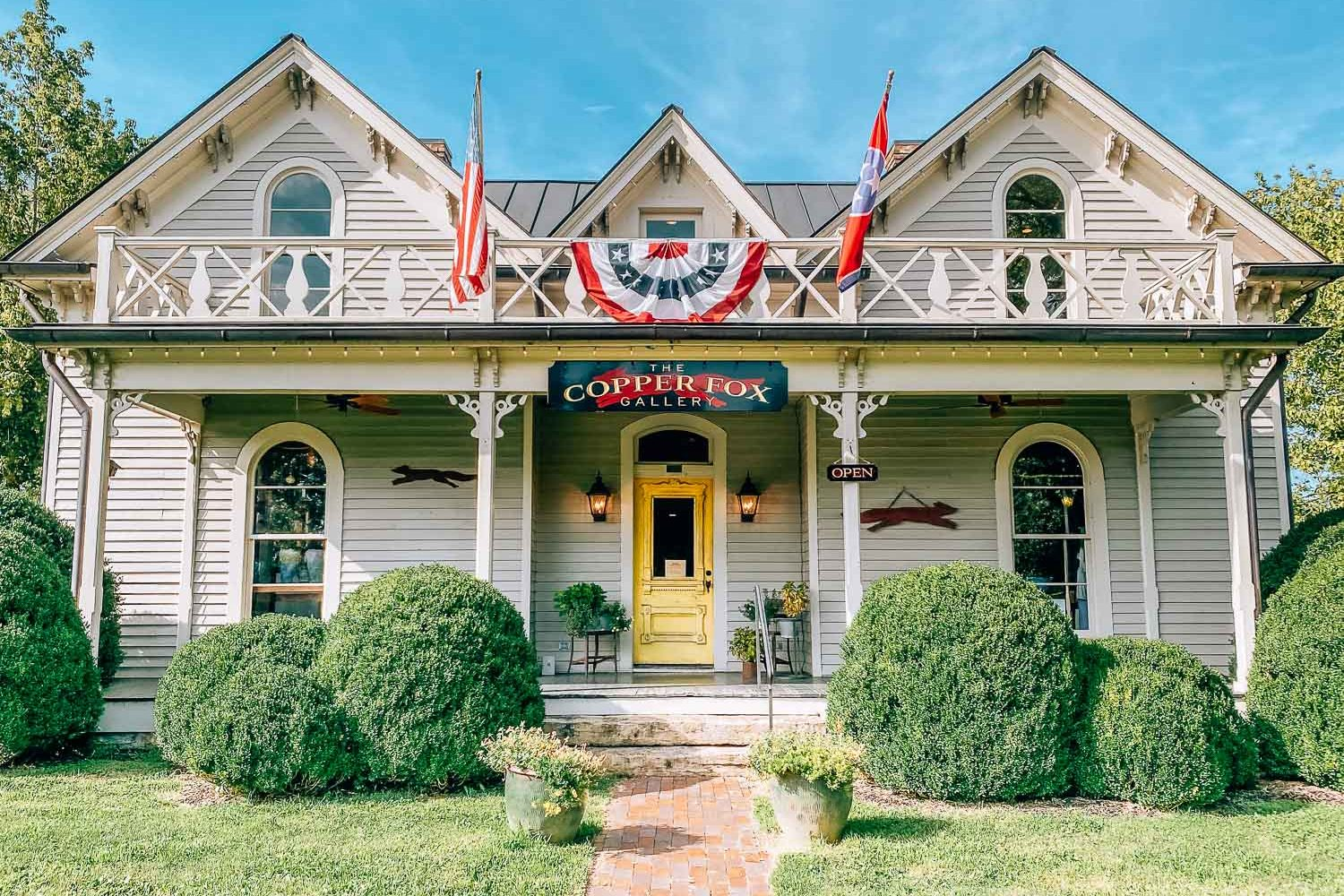 Another thing to do in Leiper's fork is visit this art gallery. This historic southern home that is now the Copper Fox Gallery in Leiper's Fork, Tennessee. There is an American flag and Tennessee state flag hanging from the upstairs balcony.