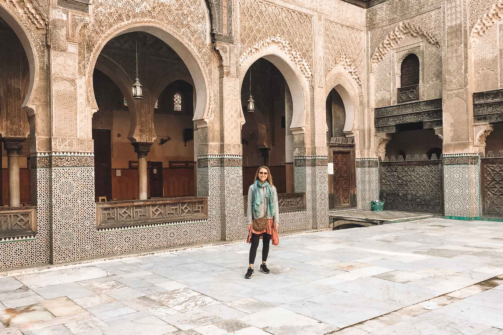 Hannah standing inside Madrasa Bou Inania in Fes Morocco - bucket list travel