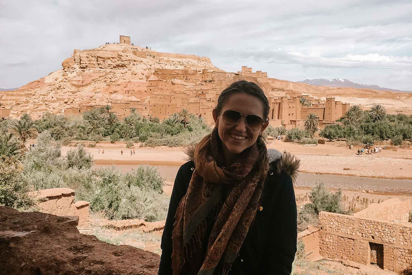 Hannah smiling at the camera with a historic kasbah in the background in Morocco - bucket list travel