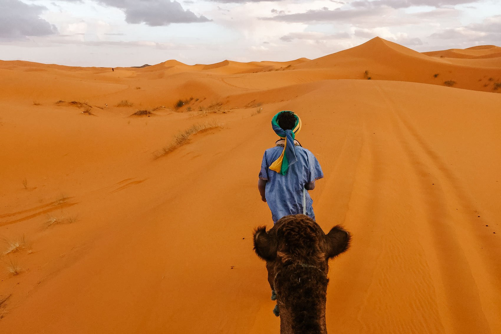 sahara desert with local pulling camel across dunes - bucket list travel one week itinerary