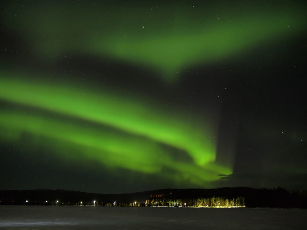 Northern lights (aurora borealis) display over a frozen lake in Lapland.