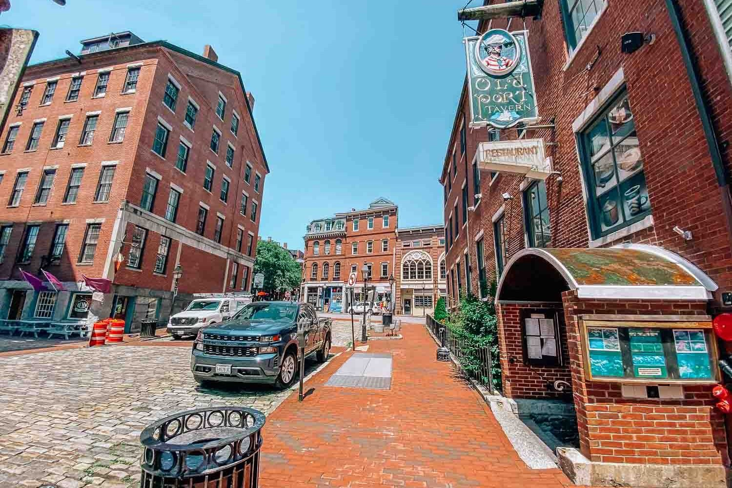 Old Port, Portland, Maine with cobblestone streets, brick sidewalks, and brick buildings. There is a sign hanging on the right that reads Old Port Tavern.