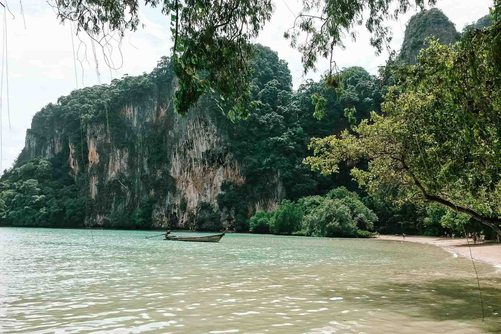 boat floating on water near limestone rocks in Railay Beach in Thailand