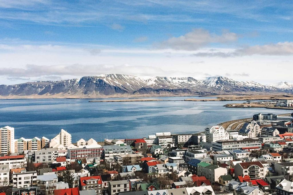 view of downtown reykjavik with ocean and mountains in the distance in iceland - bucket list travel