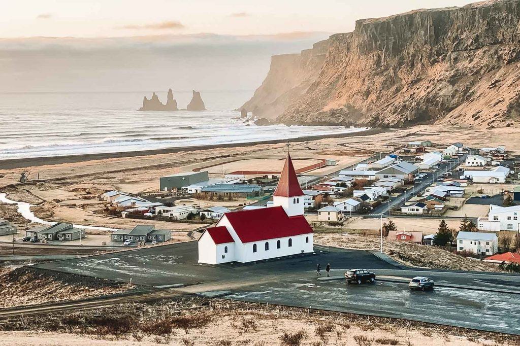 view of the small town of Vik in Iceland with a church in the foreground, houses and the ocean in the background - bucket list travel