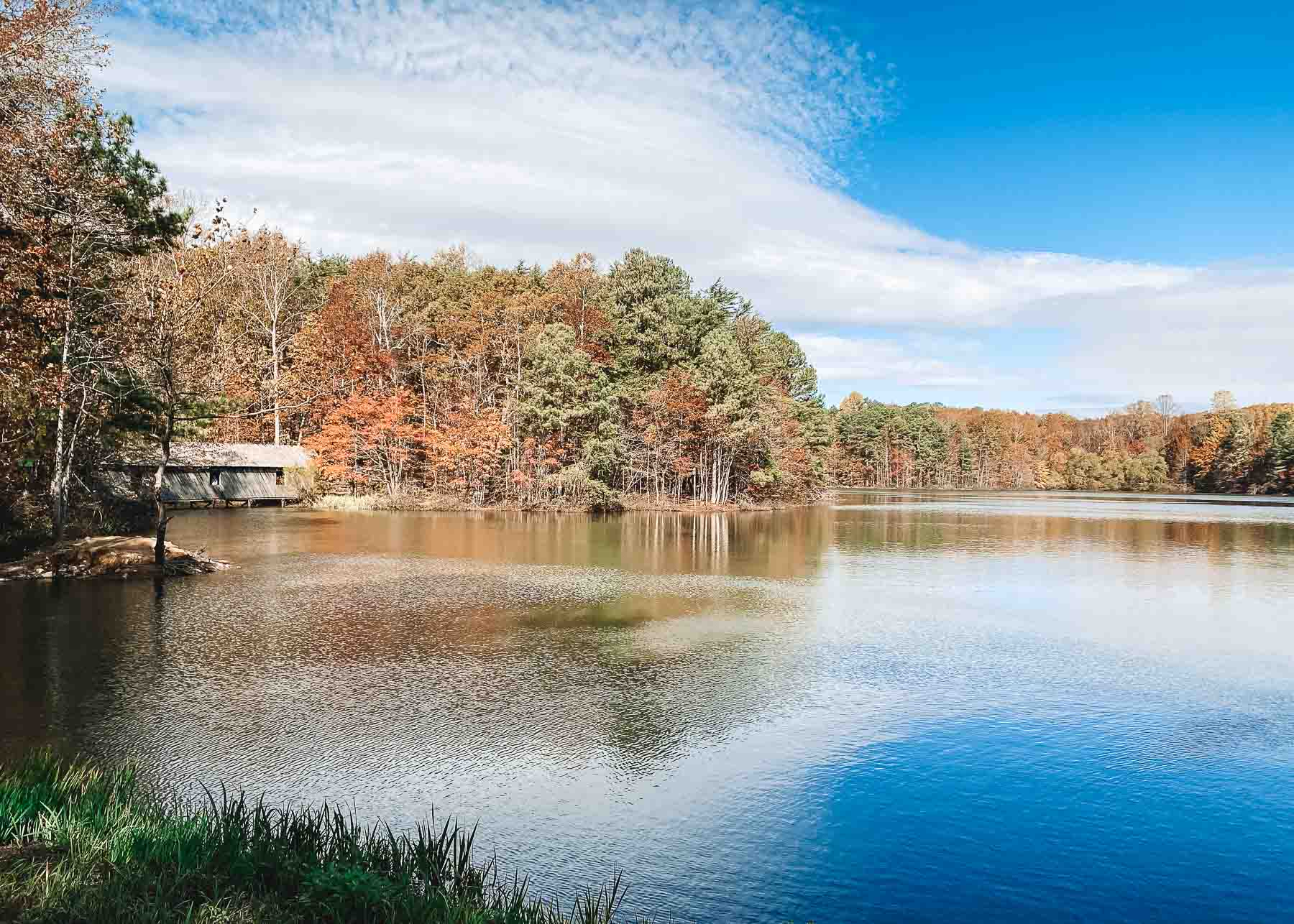 weekend road trip - lake in huntsville alabama surrounded by fall trees. there is a covered wooden bridge to the left of the lake.