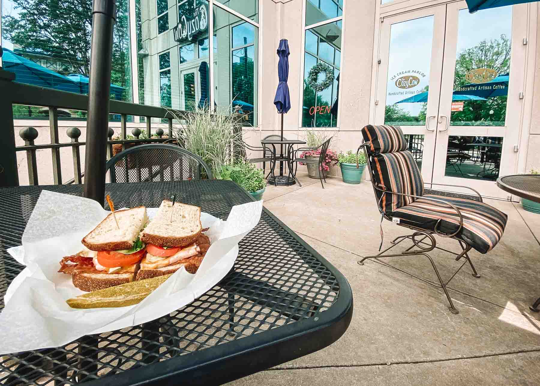 Patio seating outside Cozy Cow in Huntsville, Alabama. There is a sandwich on the left with a pickle next to it.