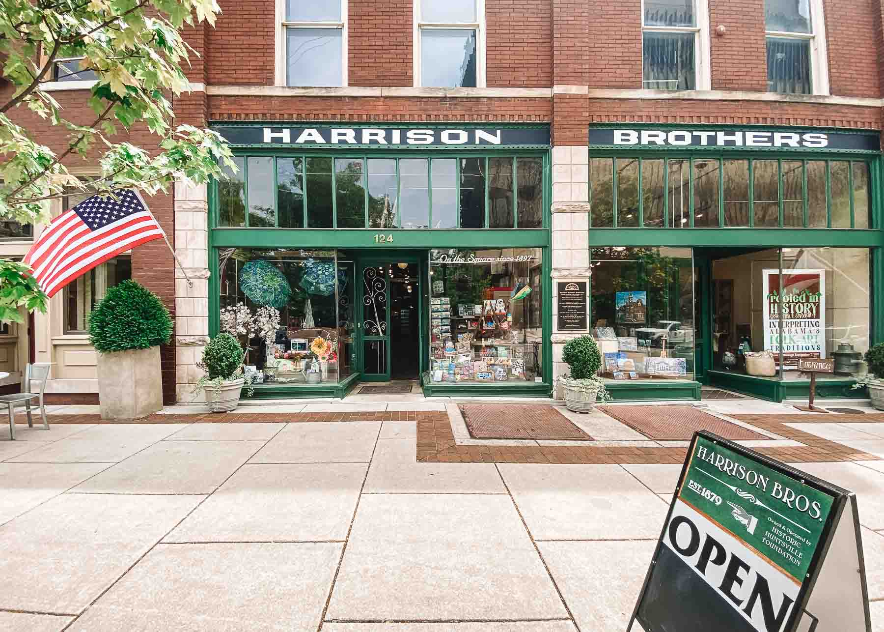 Exterior of building in Huntsville, Alabama with sign that reads Harrison Brothers. There is an American flag hanging on the left.