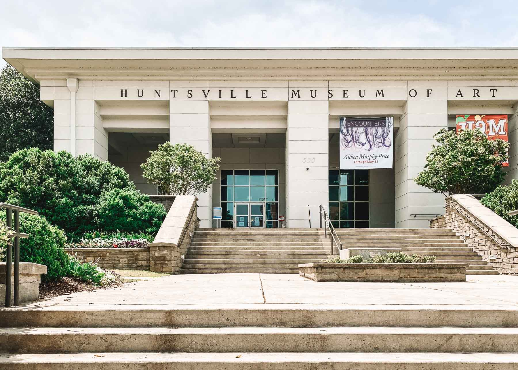 Exterior of the concrete building of the Huntsville Museum of Art. There are many. steps leading up to glass doors.