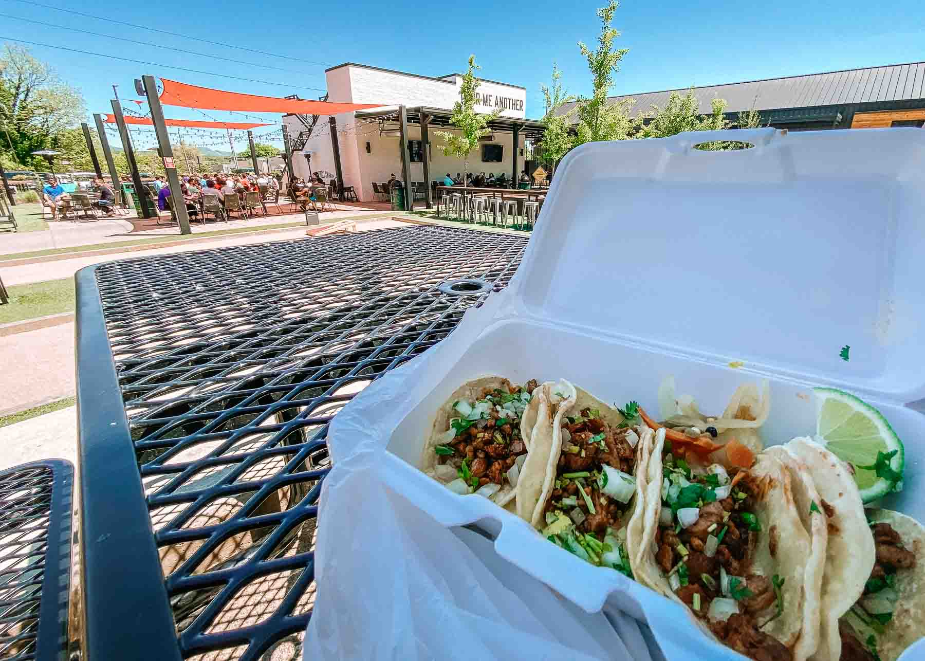 Patio dining at the Stovehouse in Huntsville, Alabama. There are 4 chicken tacos sitting on a white tray.