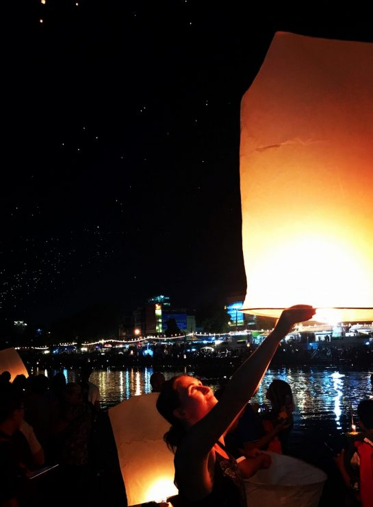 Hannah Corderman holding up a big lantern to release into the night sky during lantern festival in Chiang Mai Thailand