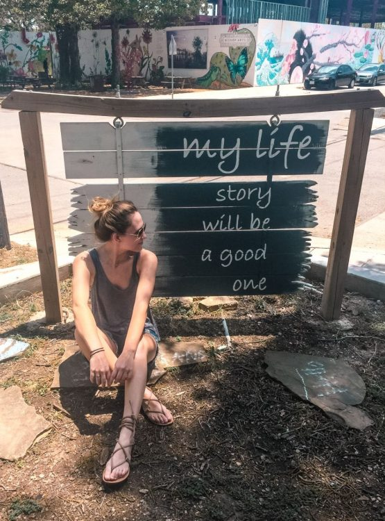 hannah sitting in front of sign in texas that says my life story will be a good one - travel bucket list