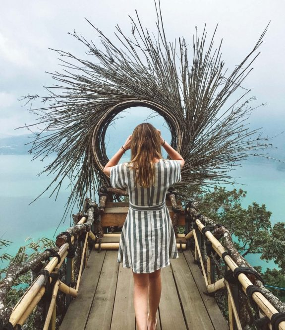 Hannah Corderman walking on boardwalk in Bali. She is wearing a dress and facing away from the camera