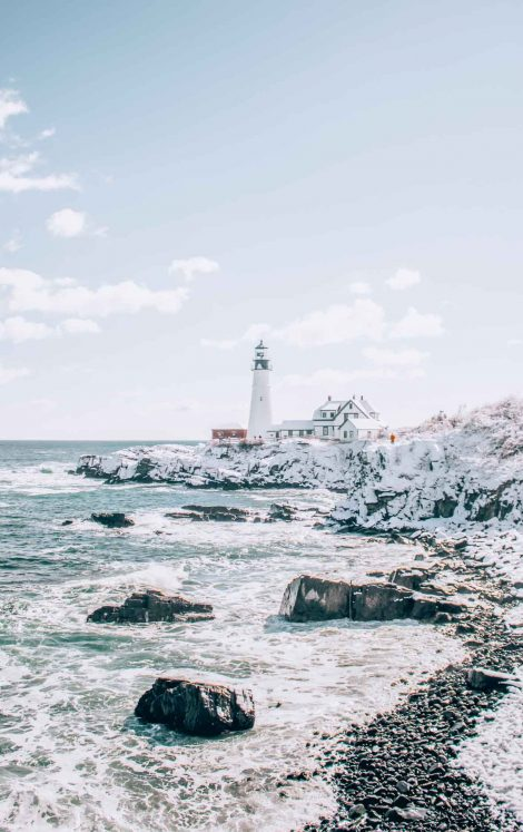 Portland Maine lighthouse in winter with snow and ocean